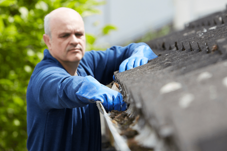 A homeowner considering gutter cleaning costs while on his roof.